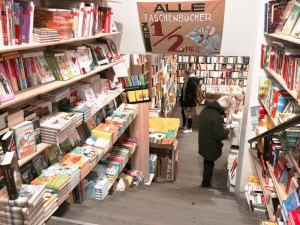 Der Buchladen, der fast ausschließlich Mängelexemplare verkauft, lädt zum Stöbern ein. Eine Treppe, links und rechts von Büchern eingefasst, führt in zwei weitere Verkaufsebenen.
