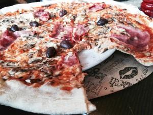 Die L'Osteria-Pizzen sind so groß, dass sie angeschnitten noch nicht ganz auf den Teller passen, Deswegen gibt es eine backpapierartigen Unterlage.