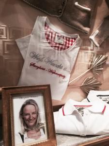 """Der Stanglwirt ist auch für seine Weißwurst-Party bekannt. Hierfür hat Maria Hauser u. a. Shirts designt. Doch es gibt auch """"normale"""" Marken im Stange-Shop zu kaufen - z. T. zu gut reduzierten Preisen. Im Hintergrund spiegelt sich eine der zahlreichen Promi-Galerien (Foto: Winderl)"""