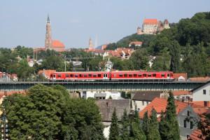 """Eine Lokalbahn über den Dächern von Landshut. Im Hintergrund St. Martin, St. Jodok und die Burg Trausnitz. Bis 31. März 2016 gilt zwischen Passau und Landshut das """"Happy-Hour-Ticket Niederbayern"""" (Foto: Copyright Deutsche Bahn AG)"""